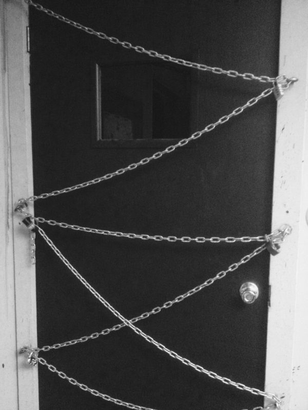 image of door secured with chains and multiple locks